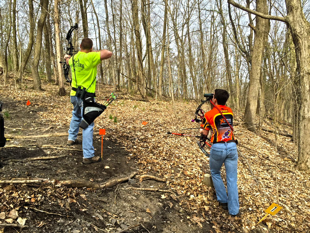 Bill Newland takes his shot on the 3D Leg of the course while Austin Ayres looks on.